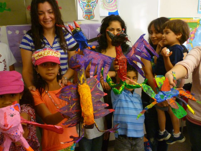Kids show off their colorful papier mache creations
